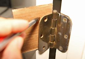 Поместите кусок картона поверх отверстий для винтов в косяке. Аккуратно выровняйте петли на картоне. Вставьте винты (они легко проколют картон) и завинтите их